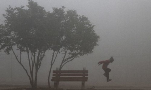 A boy plays in a park amid heavy fog on a cold morning in the northern Indian city of Chandigarh February 6, 2012. REUTERS/Ajay Verma (INDIA - Tags: ENVIRONMENT SOCIETY)
